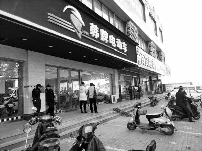 市民聚集在和平车行店前要说法,民警赶到后对店铺进行了查封。