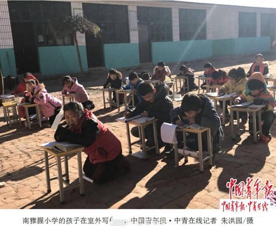 乡村小学迟未供暖 小学生教室外晒太阳取暖