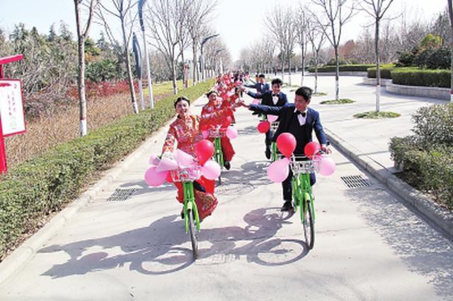 商丘举行零彩礼集体婚礼 10对新人骑自行车绕行公园