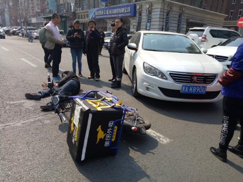 哈尔滨一送餐小哥骑车逆行撞上轿车 受伤倒地