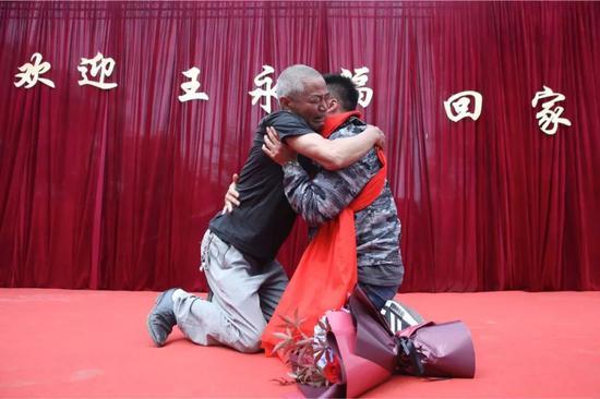 2019年5月14日,四川崇州市三江镇王桥村。认亲仪式上,王永福和父亲跪着相拥而泣。 新京报记者 尹亚飞 摄