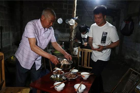 2019年5月15日,四川崇州市三江镇,王永福家。晚上,王永福的父亲烧了几个菜,正准备吃饭。 新京报记者 尹亚飞 摄