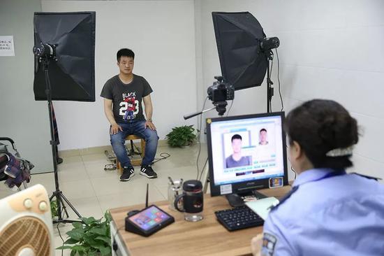 2019年5月14日,崇州市行政审批局。民警正在给王永福拍证件照,用来办理身份证。 新京报记者 尹亚飞 摄
