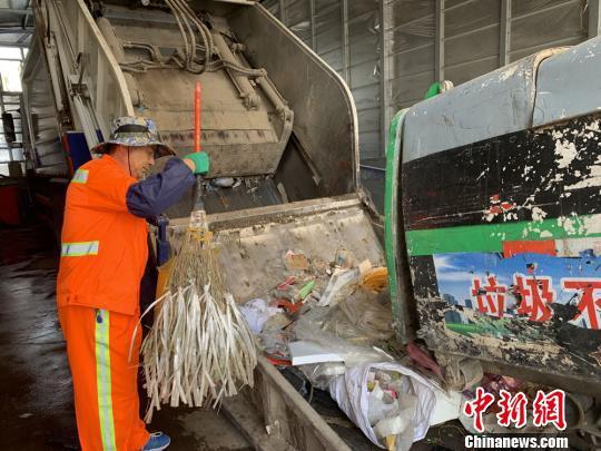 图为魏孔泽正在垃圾车旁倾倒垃圾。 高康迪 摄