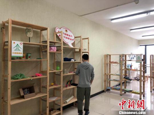 """王文达正在整理""""公益屋""""的物品。 贺劭清 摄"""