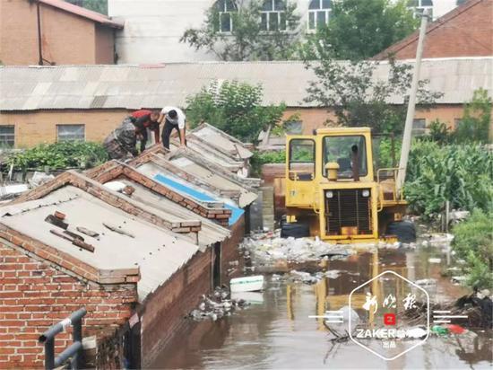 房顶上一位村民被水围困,一辆铲车将该村民从房顶救出。