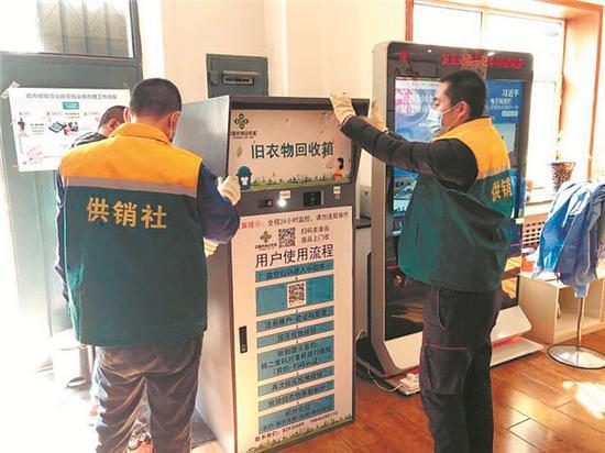 工作人员将旧衣物智能回收箱摆放到指定地点。