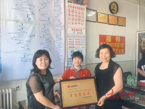 大庆福彩中心工作人员为投注站送去奖牌。