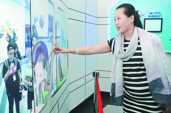 图为李欣昱在演示团队研发的液晶拼接屏设备。本报记者郭俊峰摄