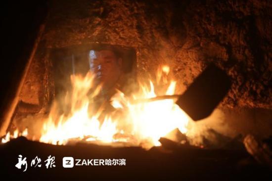 (9日,哈尔滨信托物业供热有限责任公司热源中心供暖车间内,工作人员正给两台锅炉点火起炉。)