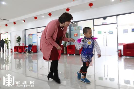 小患者牵着贾秀芳的手。东北网记者 迟亦达 摄