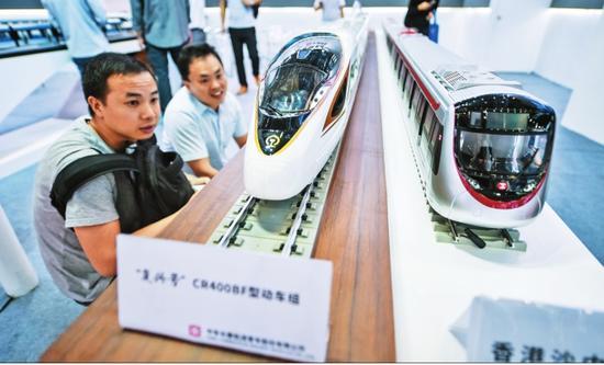 """图为在深圳举行的第十九届高交会上,参观者在中车集团的展台观看""""复兴号""""列车模型。"""
