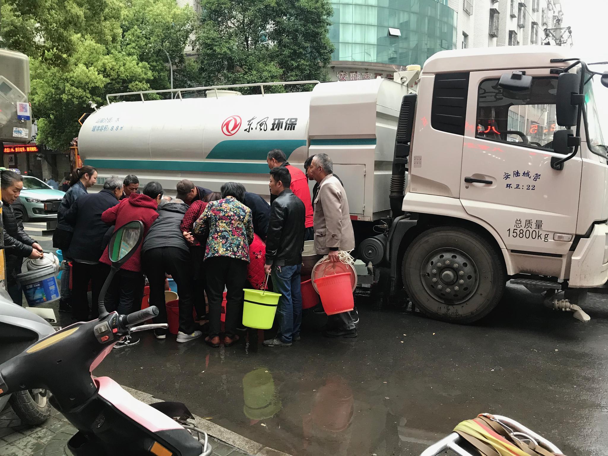 4月28日下午,在儒学路和龙门路交叉口,安陆城管部门的车辆在向附近居民发放生活用水。 陈耳生 摄