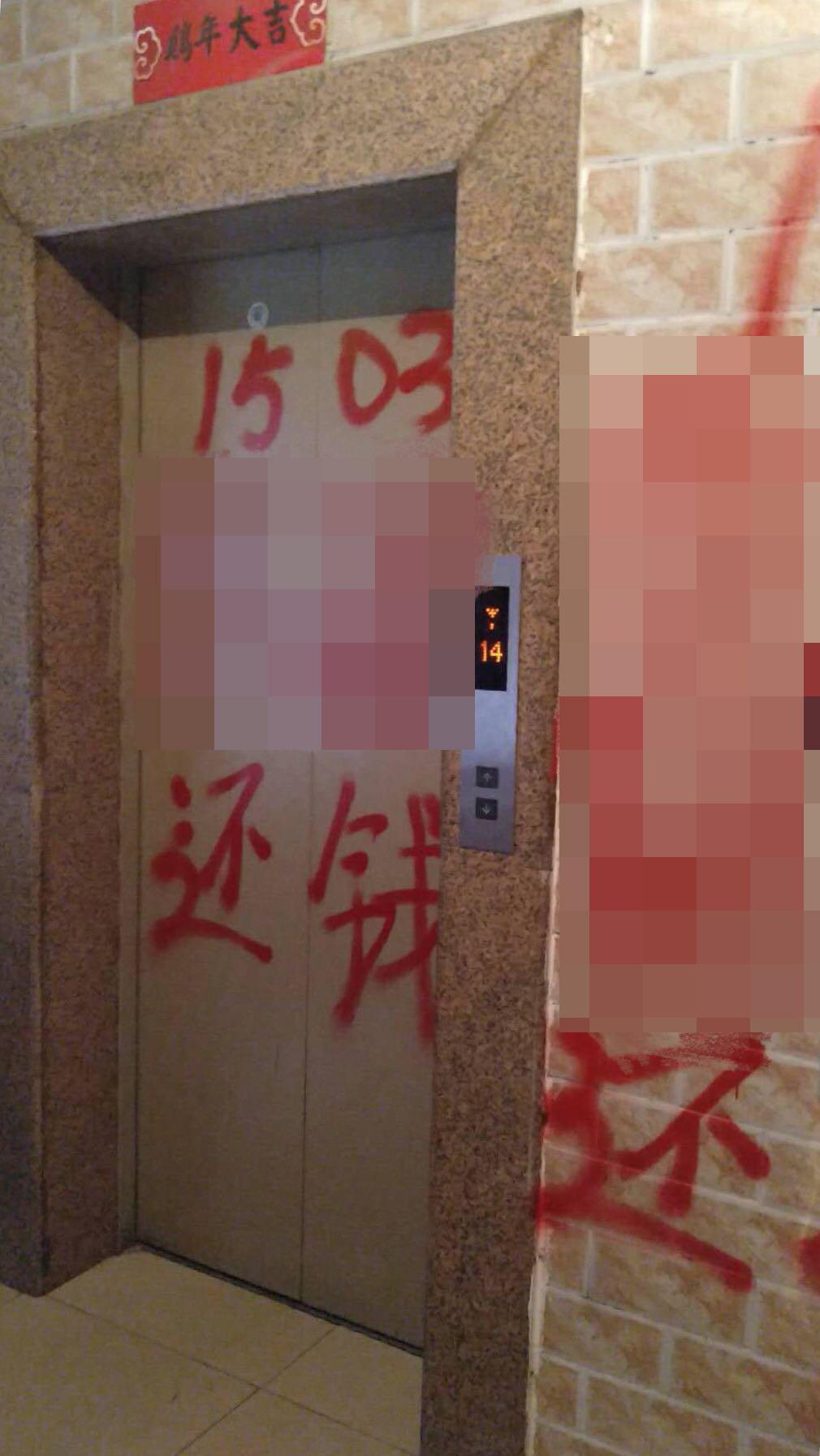 因为还不上钱,张洪家的楼道里被人喷了红色油漆。受访者供图