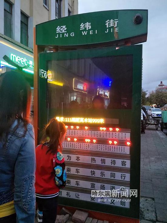 市民正在查看电子站牌上显示的公交车位置