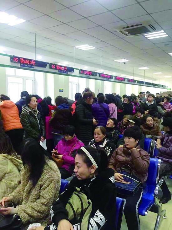 大厅内满是等待的市民,而后方有五个窗口没有开