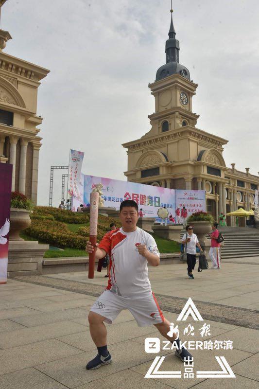 火炬手王爱中激动地展示着自己手中的北京奥运会火炬。