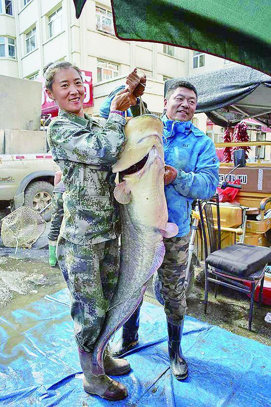 渔民董旗和妻子拿着鲇鱼。照片由虎林市委宣传部提供