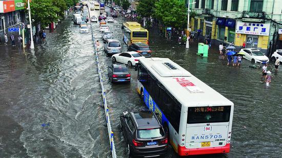 尚志大街人车涉水行。生活报记者李巍摄
