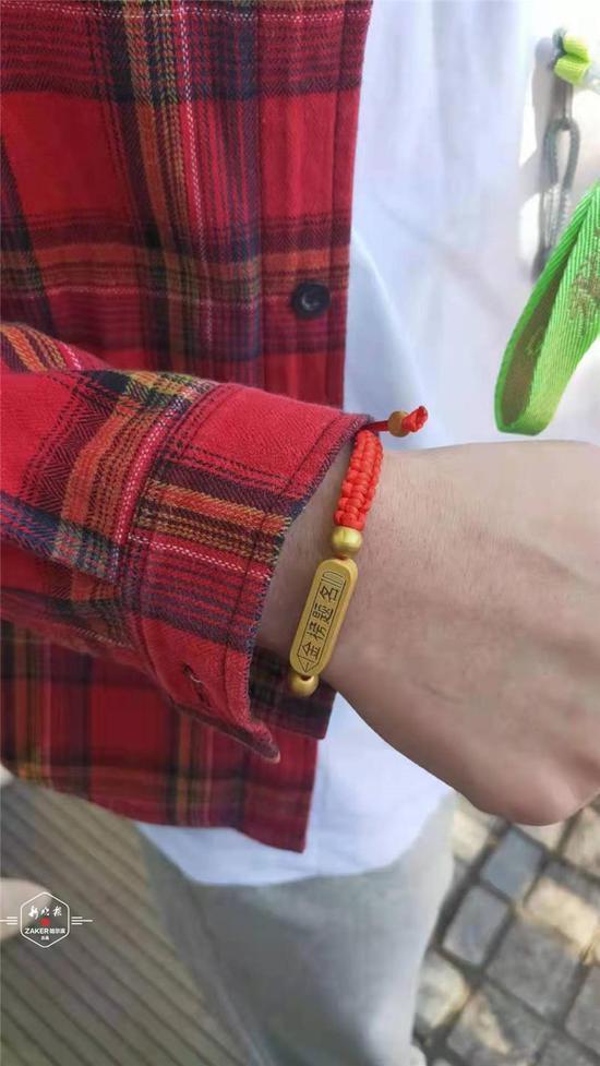 ↑ 身穿红衣的老师亲手给学生系上印有金榜题名字样的红绳,再来一个温暖的抱抱,发一块糖果,给学生讨个好彩头