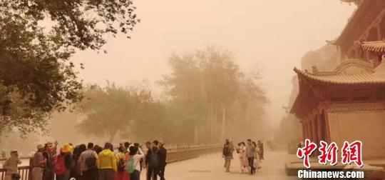 6月13日上午,地处甘肃河西走廊西端的酒泉市大部出现扬沙天气,包括敦煌在内的多地遭沙尘暴袭击。图为沙尘弥漫的世界文化遗产敦煌莫高窟。 钟欣 摄