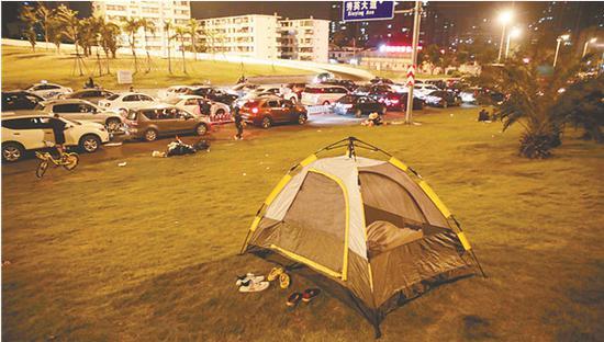 堵在三亚的游客支起帐篷过夜。中新社发