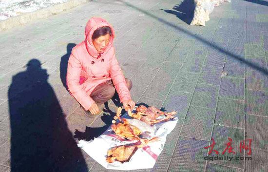 女子蹲在路边贩卖鸡、鹅。