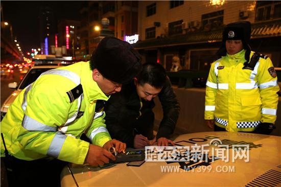 酒驾司机在处罚单上签字。