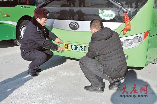 交警支队副支队长朱振清为纯电动客车车主发放我市首副新能源汽车专用号牌。