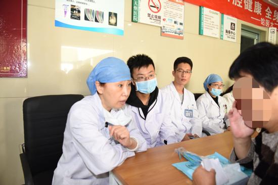 口腔内科主任王秀梅教授(左1)对患者进行问诊