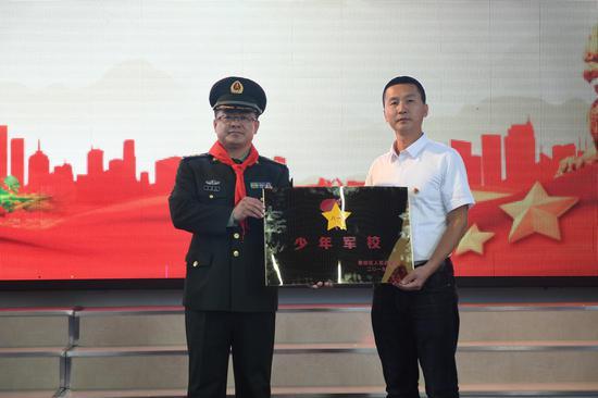 """香坊区委常委、人民武装部部长马志刚为香和小学授予""""少年军校""""称号"""