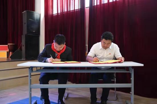 """龙飞国防教育中心主任刘永与香和小学校长赵承签订了《""""国防教育进校园""""共建共育协议》"""