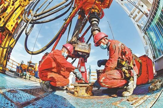 大庆页岩油二号试验区钢铁1205钻井队工人在钻井平台上调试钻机。
