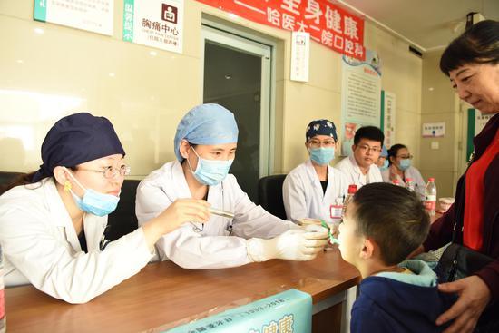 儿童口腔科副主任谢晓华(左2)为小患儿进行检查
