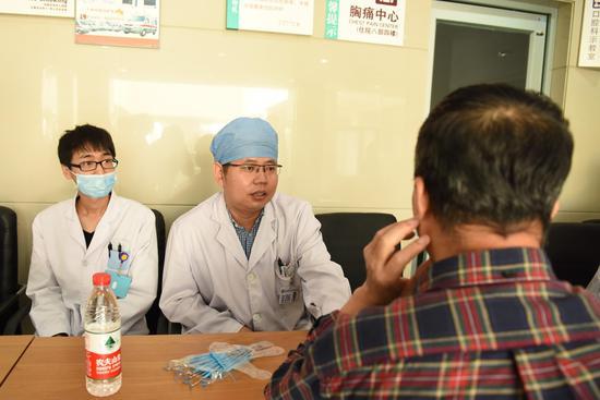 口腔种植科副主任胡那日苏(左2)为患者解答疑惑