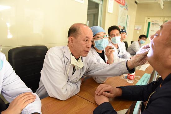 口腔修复科袁峰副教授为患者进行检查