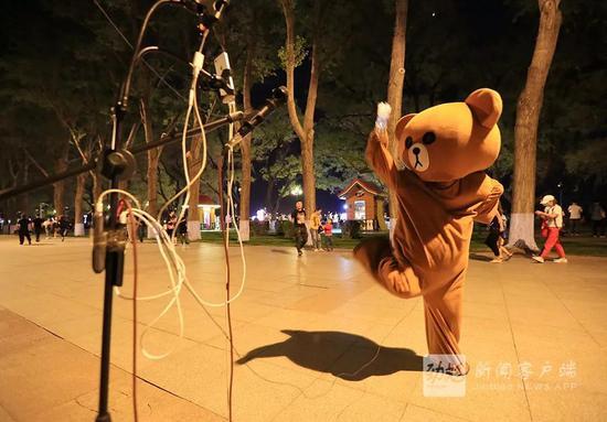 一位穿着小熊衣服的男孩,戴着耳麦在直播跳舞,他奇特的造型,让路过的