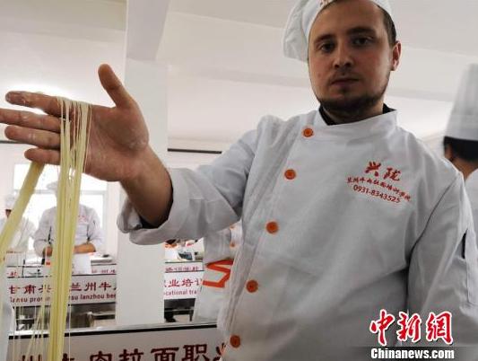 """图为来自哈萨克斯坦的留学生赤龙展示拉出的""""毛细""""面型。毛细是牛肉面中最细的一道面食,成型后""""细如发丝""""。史静静 摄"""
