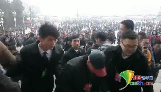 全国政协委员赵本山(中)刚到人民大会堂外,便被记者包围。中国青年网记者 晋凯 摄