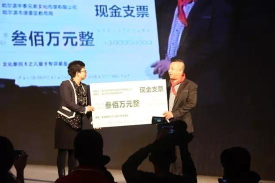 中泰兄弟文化传媒董事长姜宏斌向道里区捐助300万元文化惠民儿童卡,道里区教育局副局长刘亚萍接受捐赠