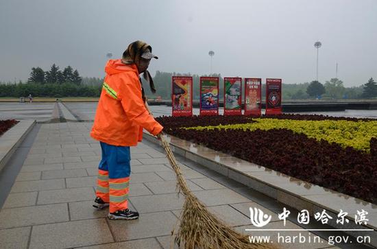 环卫工人在市政府广场清扫作业。
