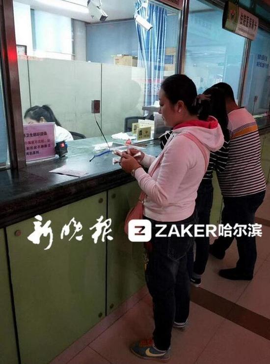 """刘晓姣正在将善款存入""""小蘑菇""""的住院押金里"""