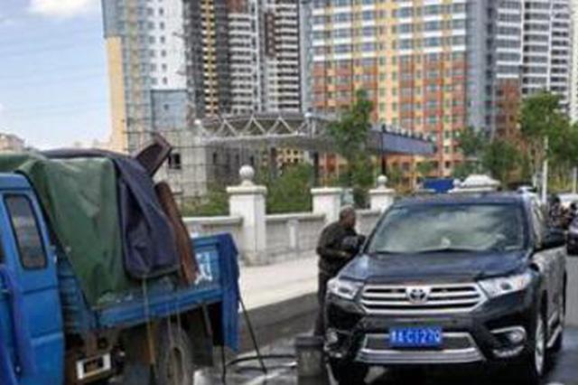 路边洗车摊正在占道洗车。