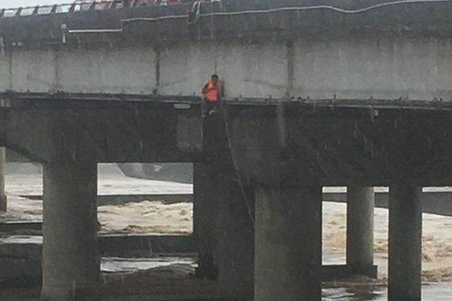 男子钓鱼遇洪水被冲50米爬上桥墩 消防紧急营救