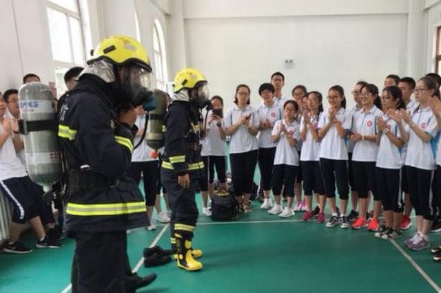 穿上防护服登上消防车 高中生走进消防队上安全课