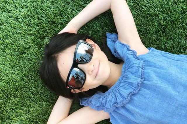 奥莉躺草坪露甜美笑容 大墨镜遮脸酷帅十足