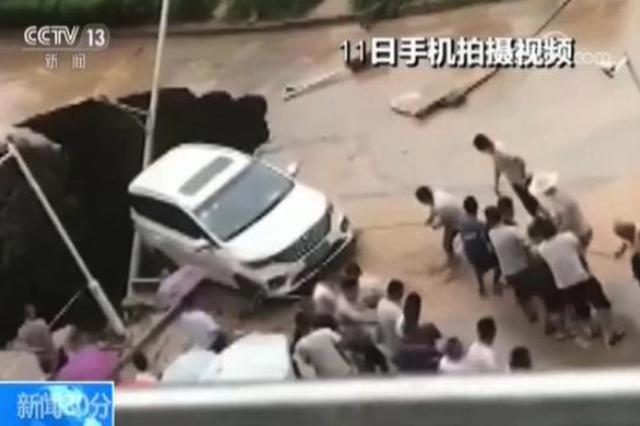 陕西延安暴雨导致路面塌陷汽车悬空 众人拉绳施救