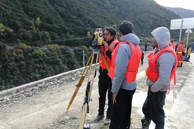 监测人员踩着泥泞道路转移观测点。昌都市水文局图