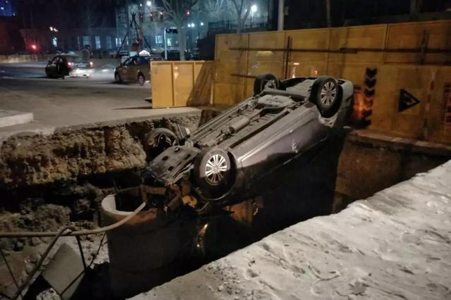 昨晚冰城一轿车撞飞围挡倒悬在坑口 车里还有一男