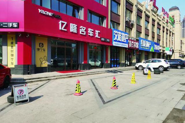 哈市群力人行道商家私设停车桩 市民只能绕桩走